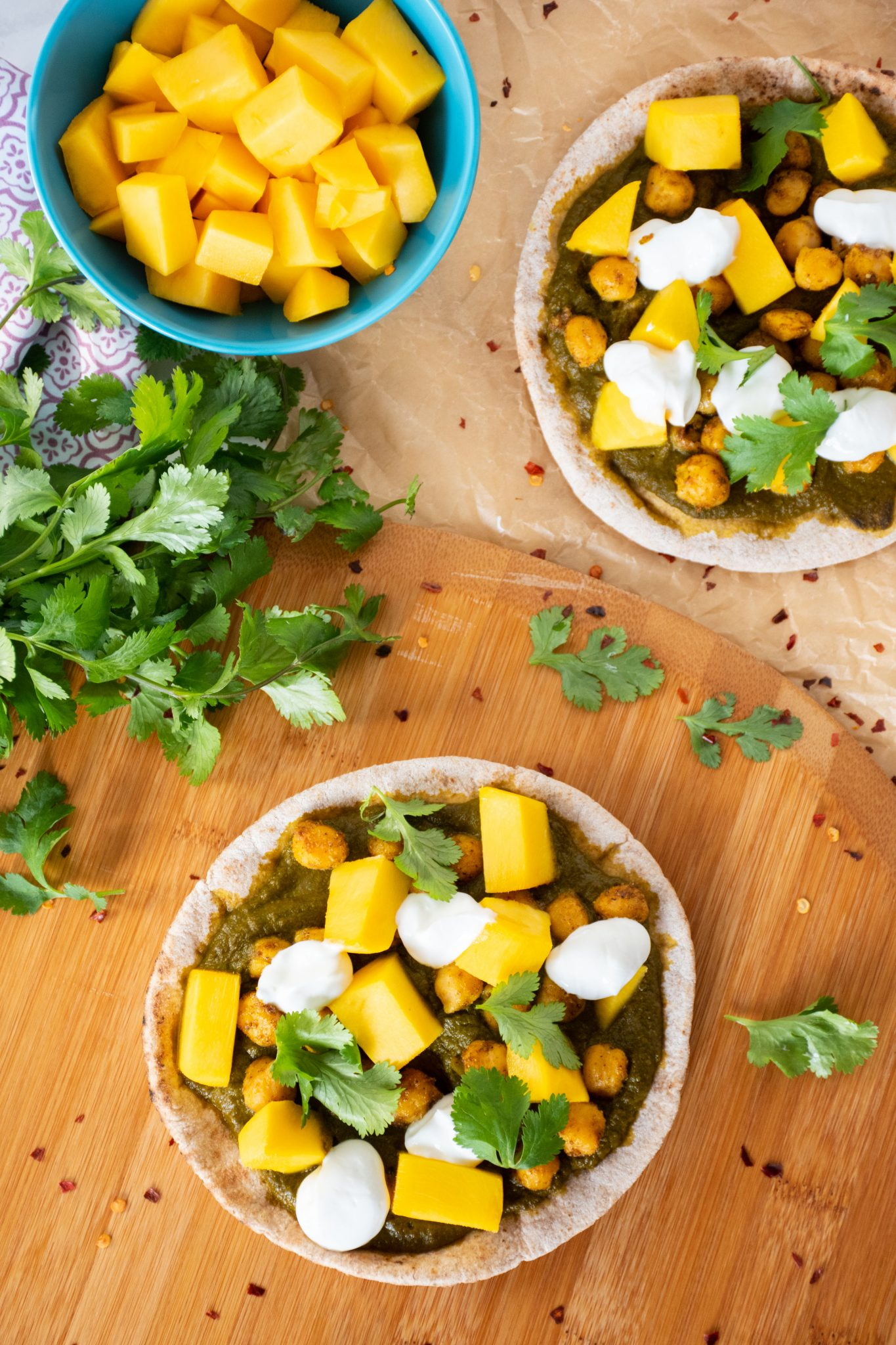 Overhead shot of pizza with spinach sauce, chickpeas, and mangoes on mini pitas.