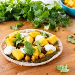pizza with spinach sauce, chickpeas, and mangoes on a mini pita.