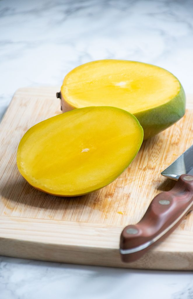 Whole mango, with one slice removed