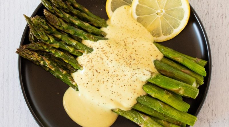 Plate of asparagus drizzled with sauce.
