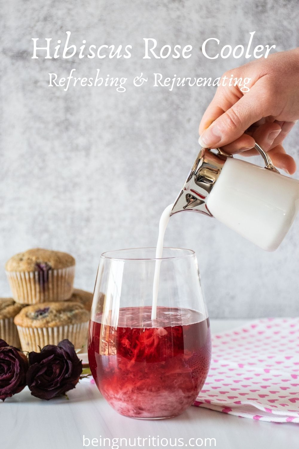 Glass of red tea with coconut milk being poured in. Text overlay: Hibiscus Rose Cooler; Refreshing & Rejuvenating.