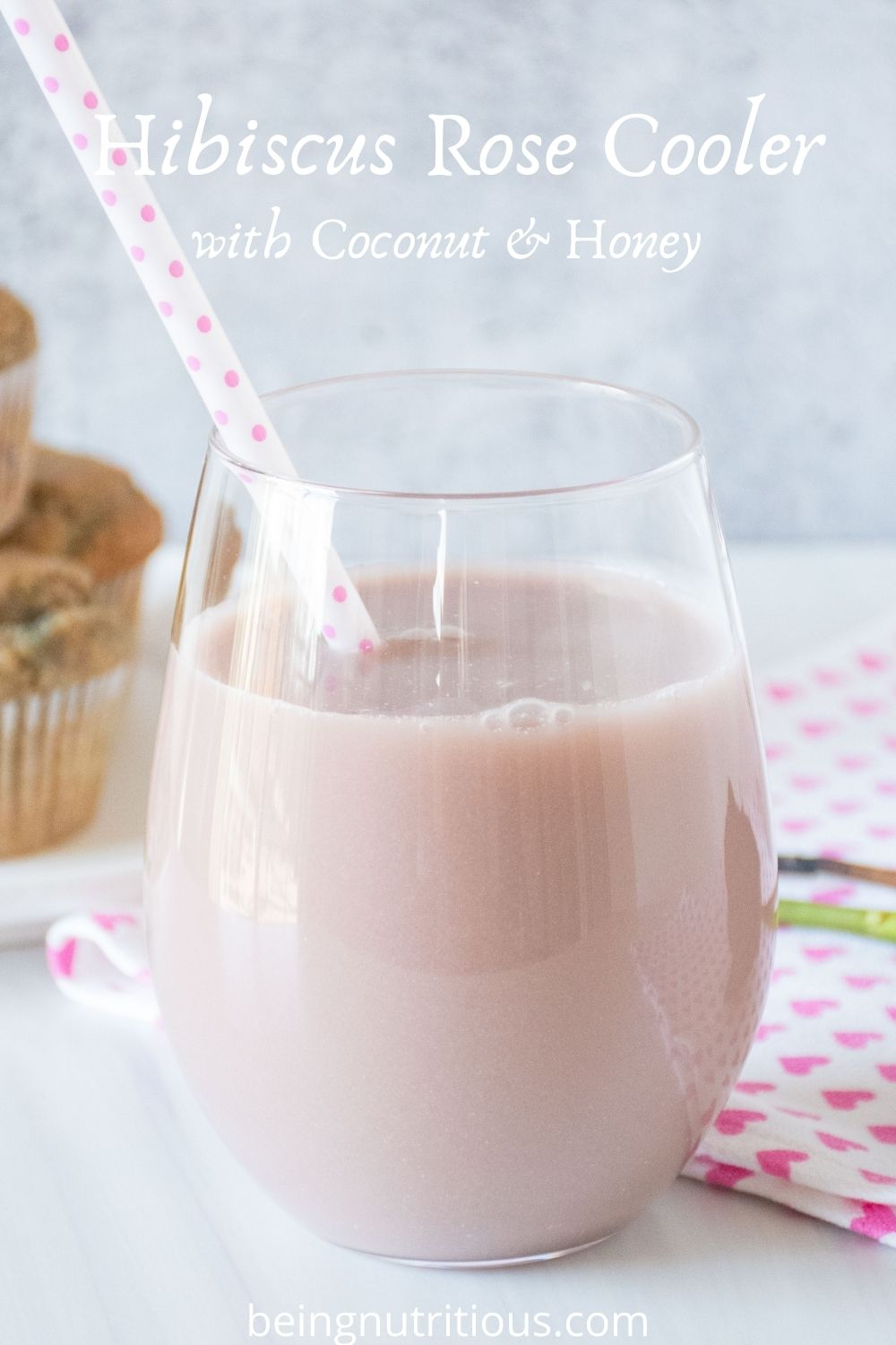 Glass of pink beverage. Text overlay: Hibiscus Rose Cooler with Coconut & Honey.
