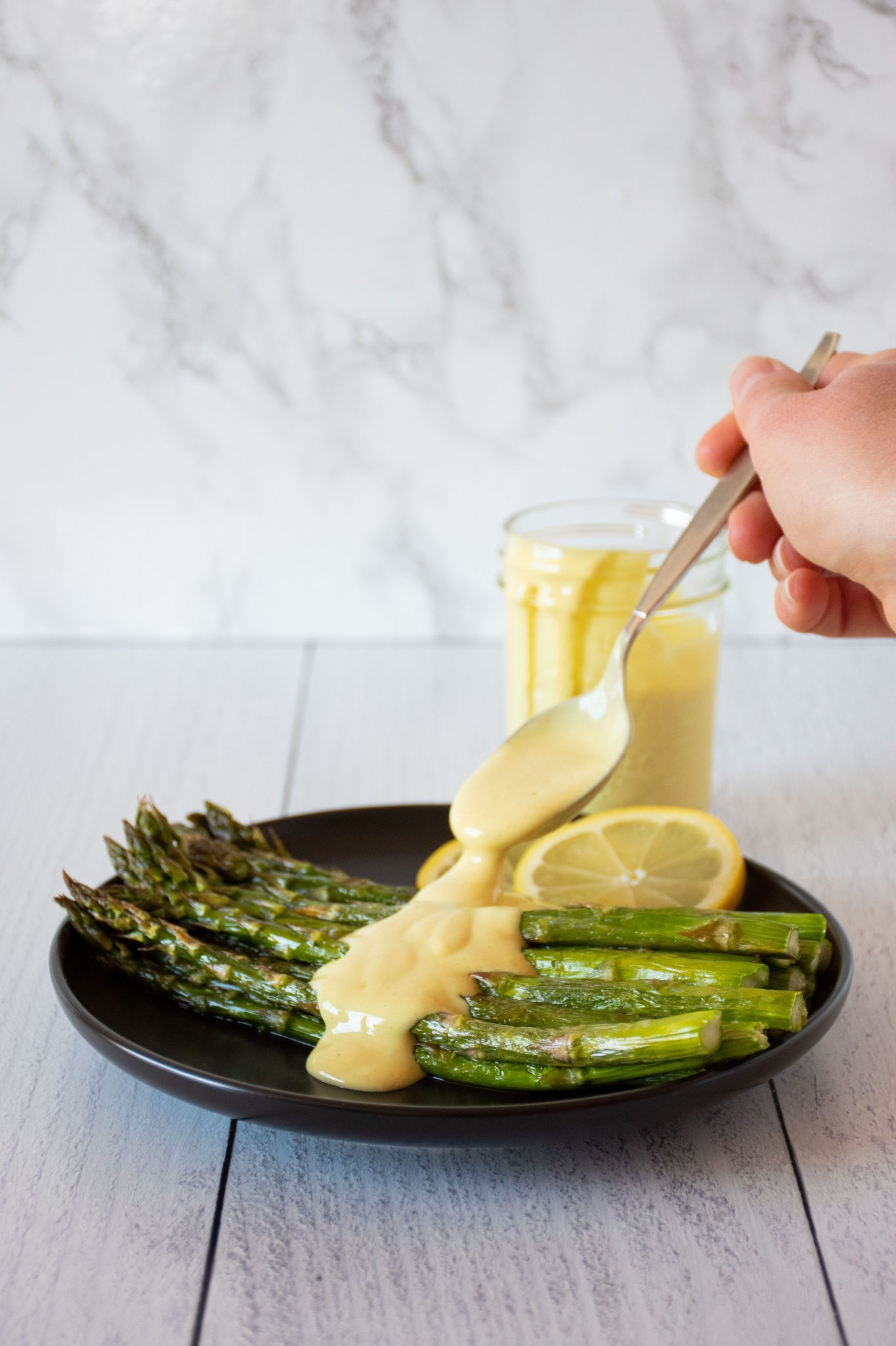 Plate of asparagus being drizzled with sauce.