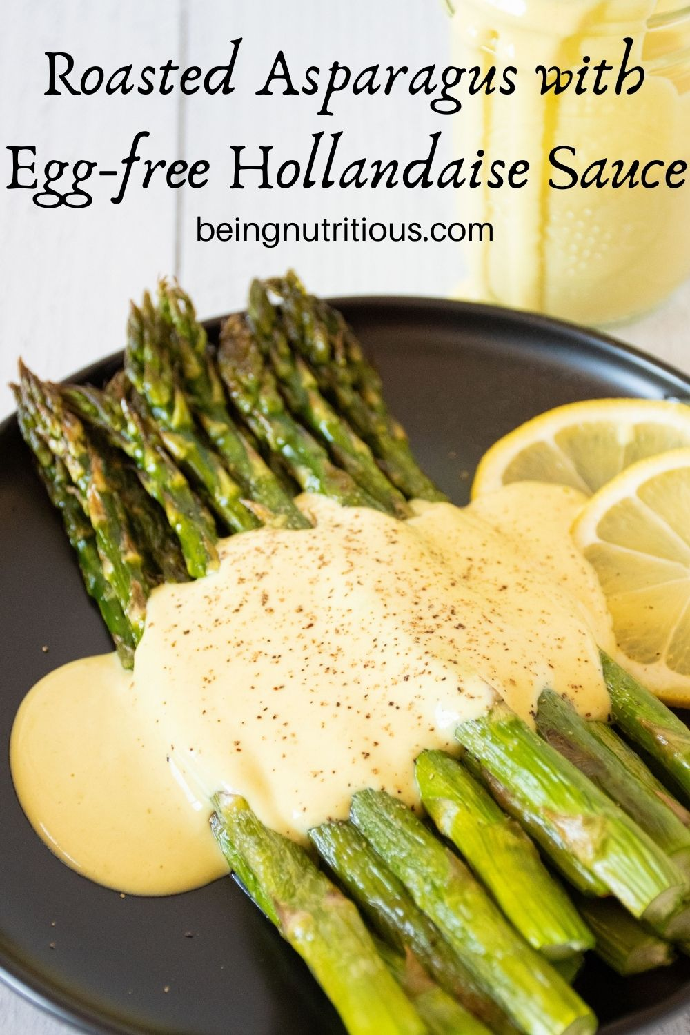 Plate of asparagus drizzled with sauce. Text overlay: Roasted Asparagus with Egg free Hollandaise Sauce.