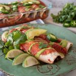 Two enchiladas on a plate, with cilantro, lime slices, jalapeno slices, and avocado.