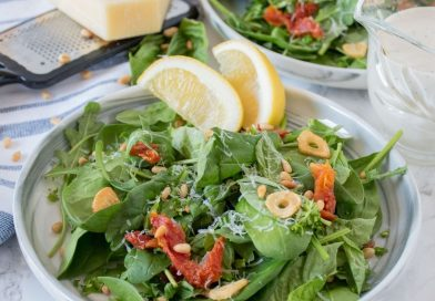 Plate of salad with sundried tomatoes, pine nuts, fried garlic, and dressing.