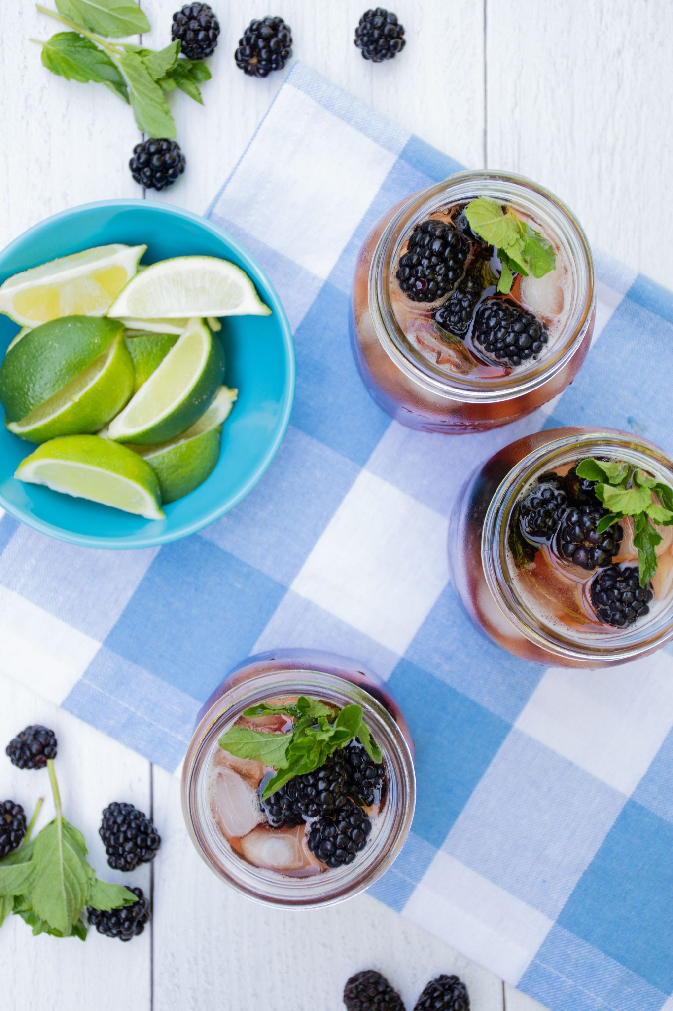Overhead shot of iced tea in 3 Mason jars, with ice, blackberries, and mint. Small bowl of lime slices to the side.