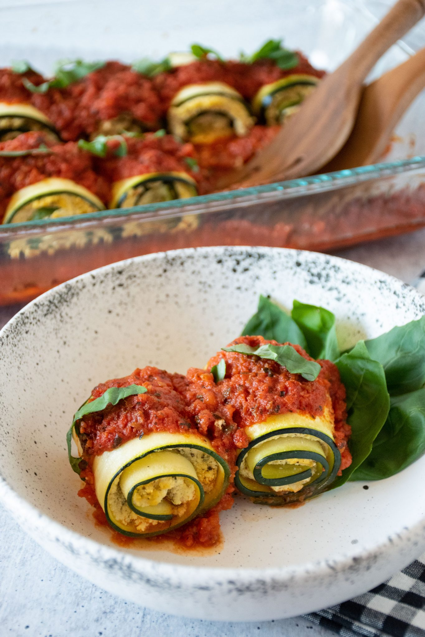 Two zucchini rolls in a bowl, with pan of rolls in background.