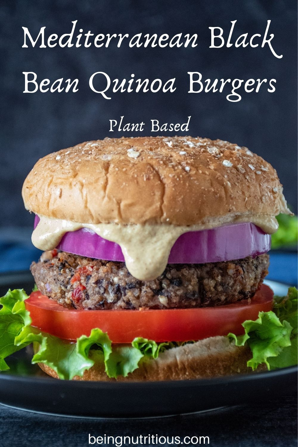 Bean burger on a bun, with onions, tomatoes, lettuce and sauce dripping out. Text overlay: Mediterranean Black Bean Quinoa Burgers; Plant Based.