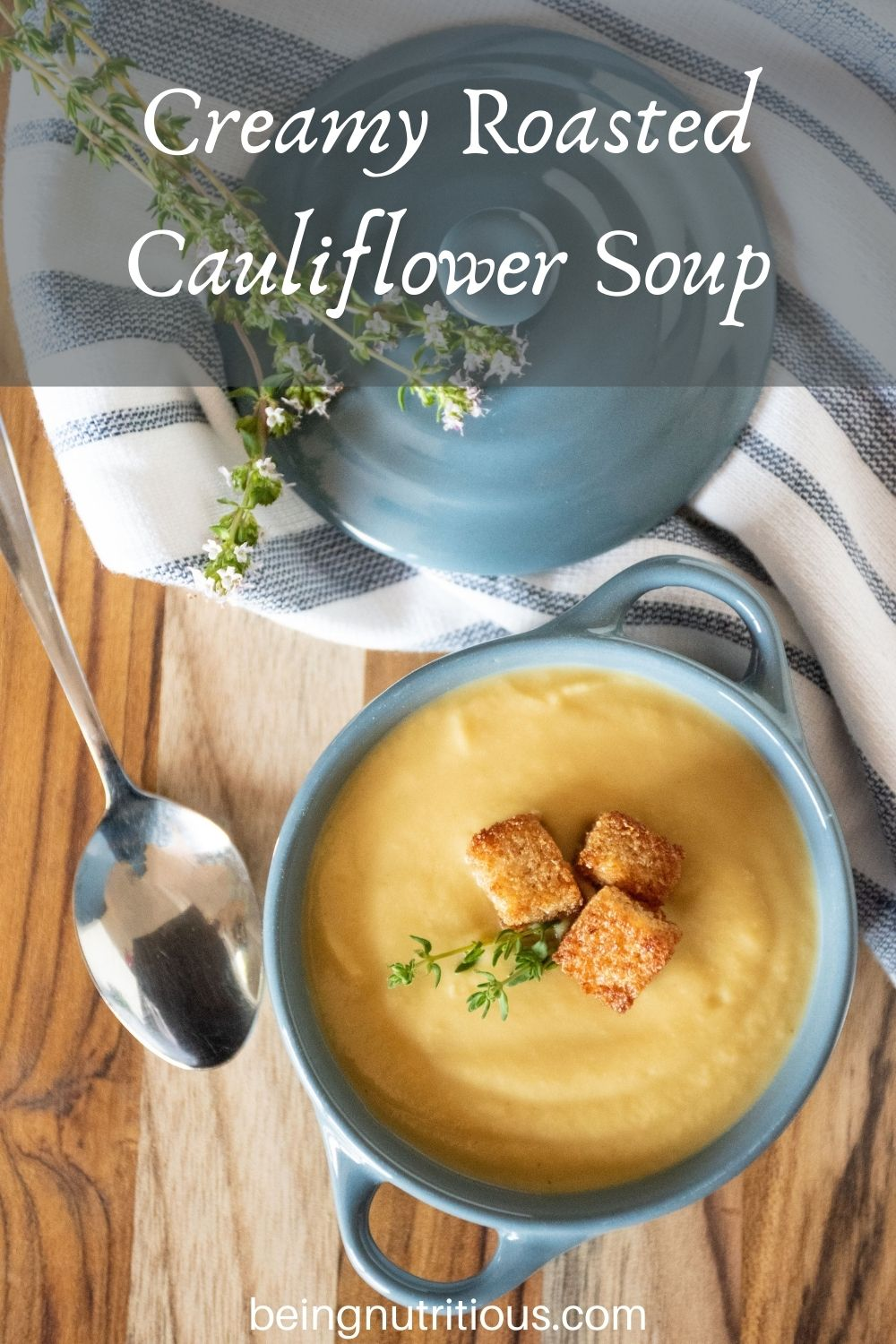 Small bowl of soup with croutons and fresh thyme. Text overlay: Creamy Roasted Cauliflower Soup.