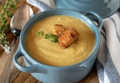 Small bowl of soup with croutons and fresh thyme.