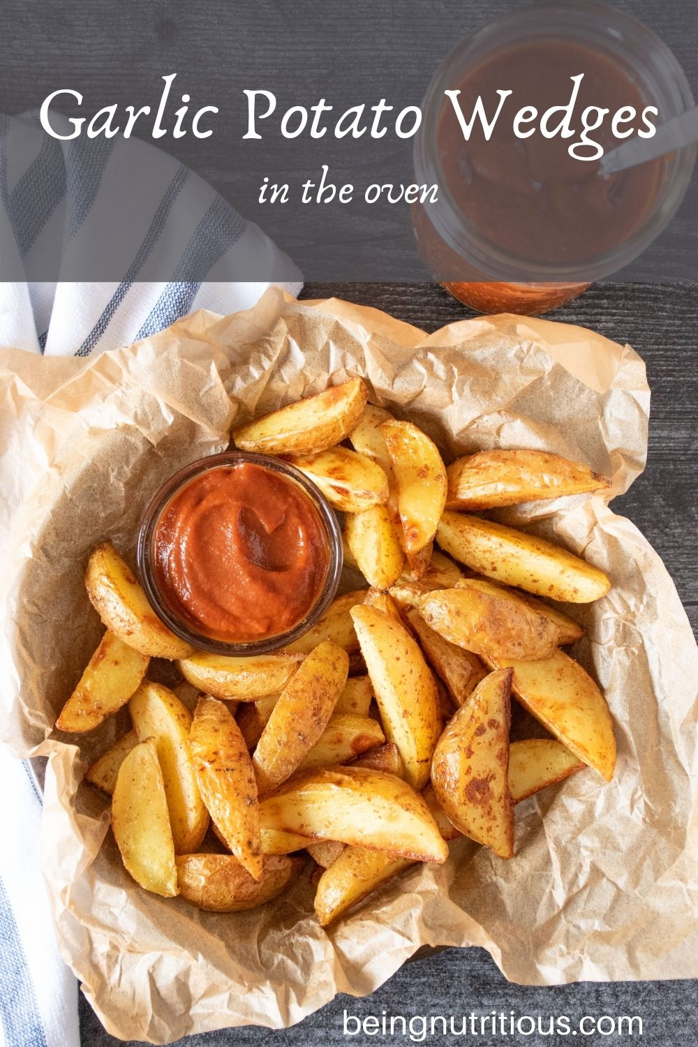 Basket of potato wedges with a small bowl of ketchup. Text overlay: Garlic Potato Wedges in the Oven.