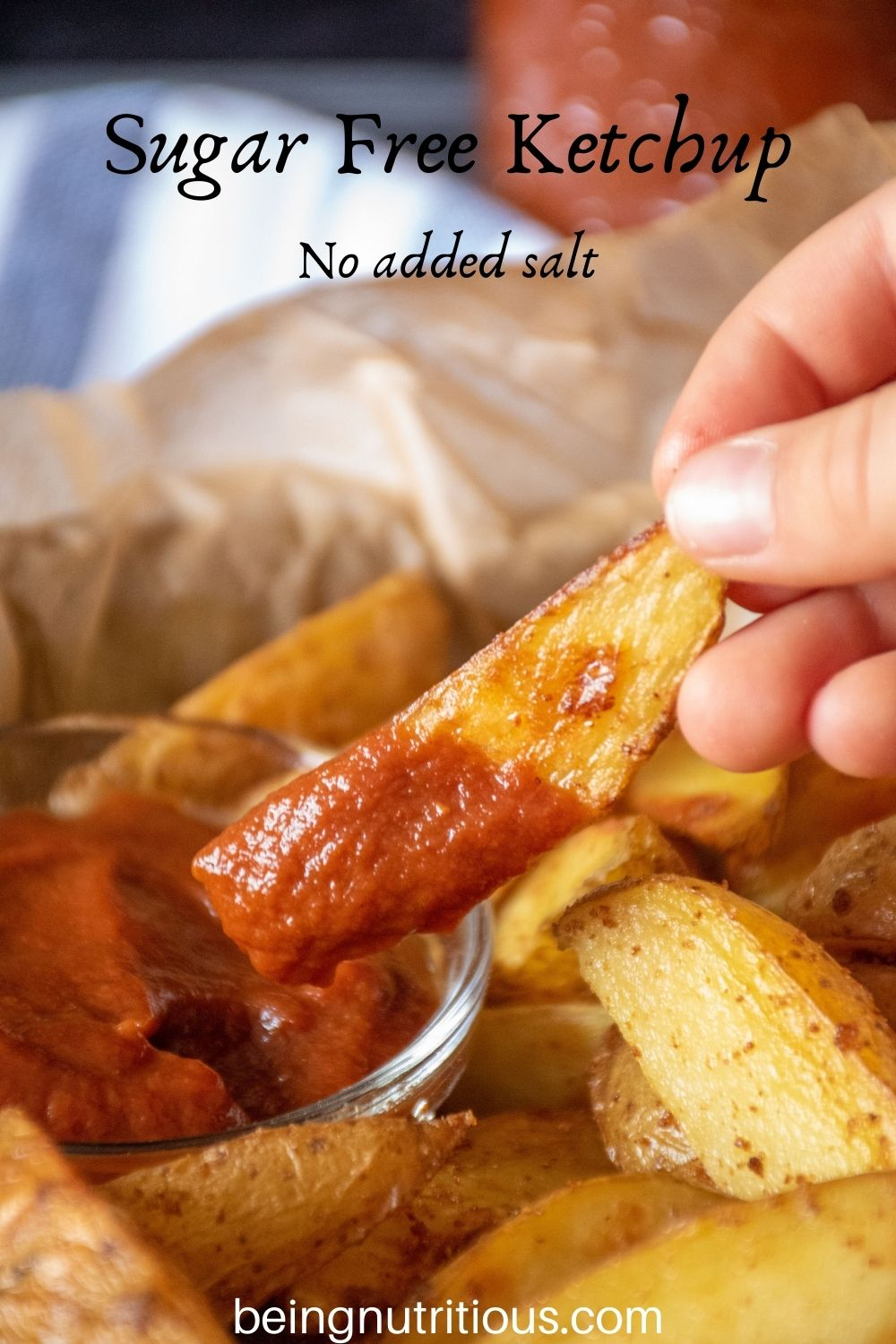 Hand holding a potato wedge, dipped in ketchup. Text overlay: Sugar Free Ketchup; No added salt.