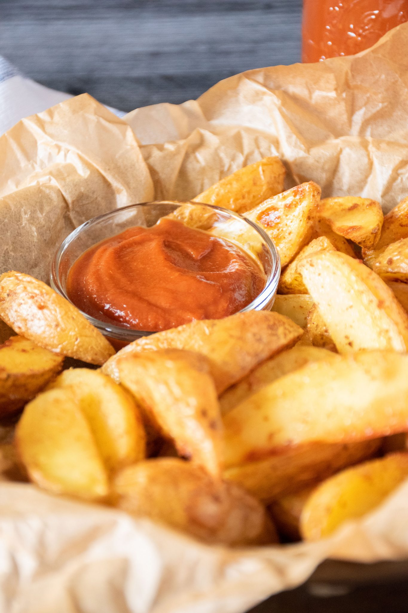 Basket of potato wedges with a small bowl of ketchup