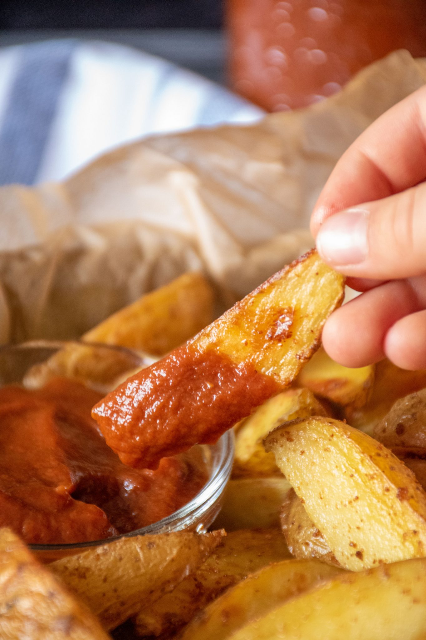 Hand holding a potato wedge, dipped in ketchup.