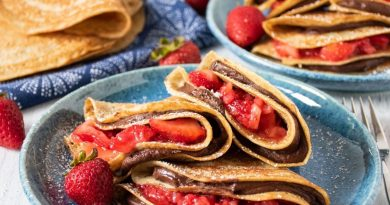 Plate of 3 crepes stuffed with chocolate dip and strawberries.