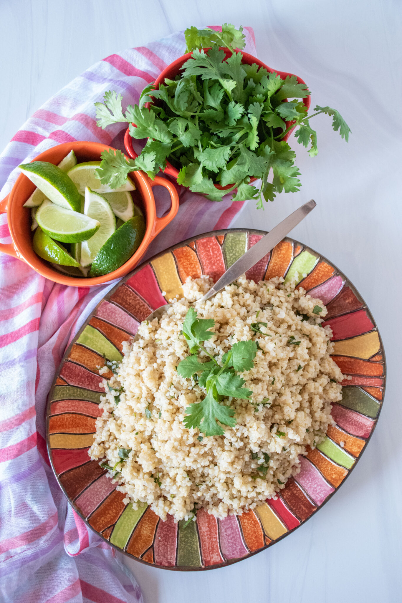 Overhead picture of quinoa on a plate, with small bowls of limes slices and fresh cilantro above.