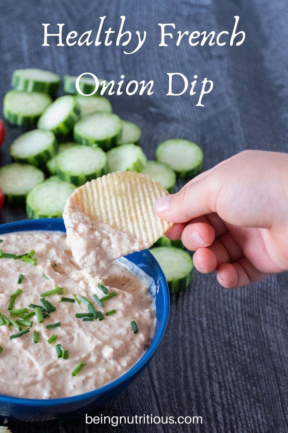Bowl of dip with cucumber slices in background. Hand holding a chip with dip on it above bowl. Text overlay: Healthy French Onion Dip