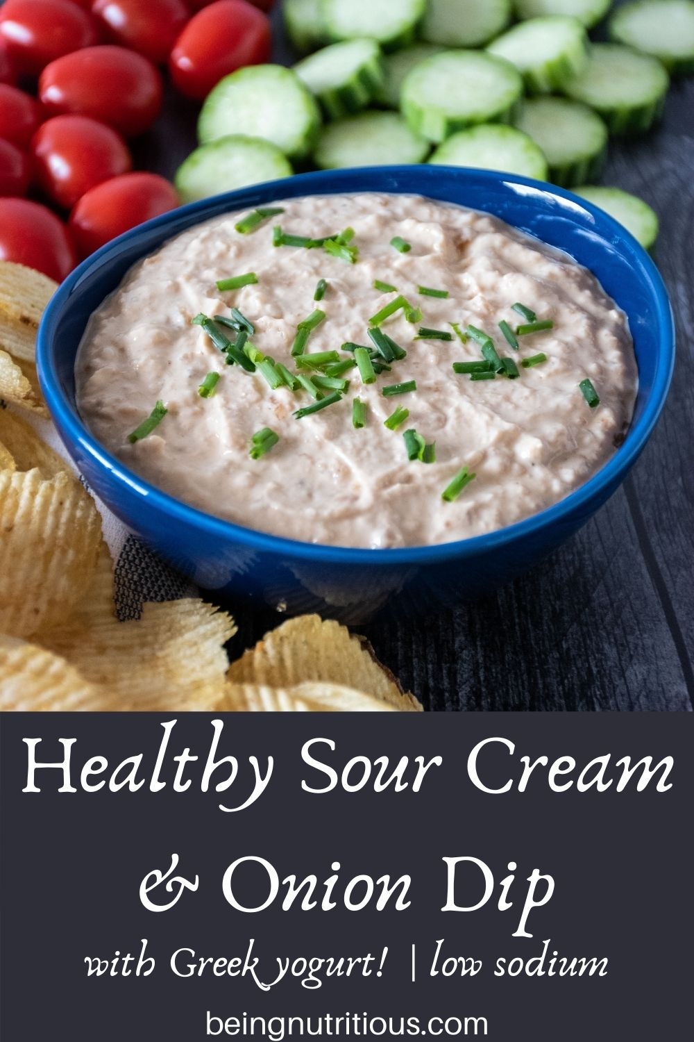 Bowl of dip, surrounded by chips, baby tomatoes, and cucumber slices. Text overlay: Healthy Sour Cream and Onion Dip, with Greek yogurt, low sodium.