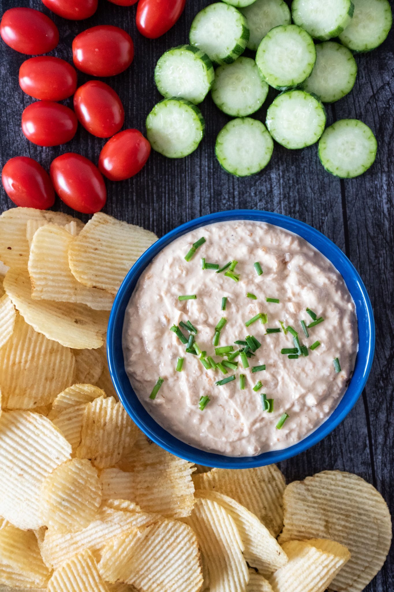 Overhead picture of bowl of dip, surrounded by chips, baby tomatoes, and cucumber slices.