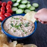 Bowl of dip, surrounded by chips, cucumber slices, and baby tomatoes. Hand holding a chip with dipping it.