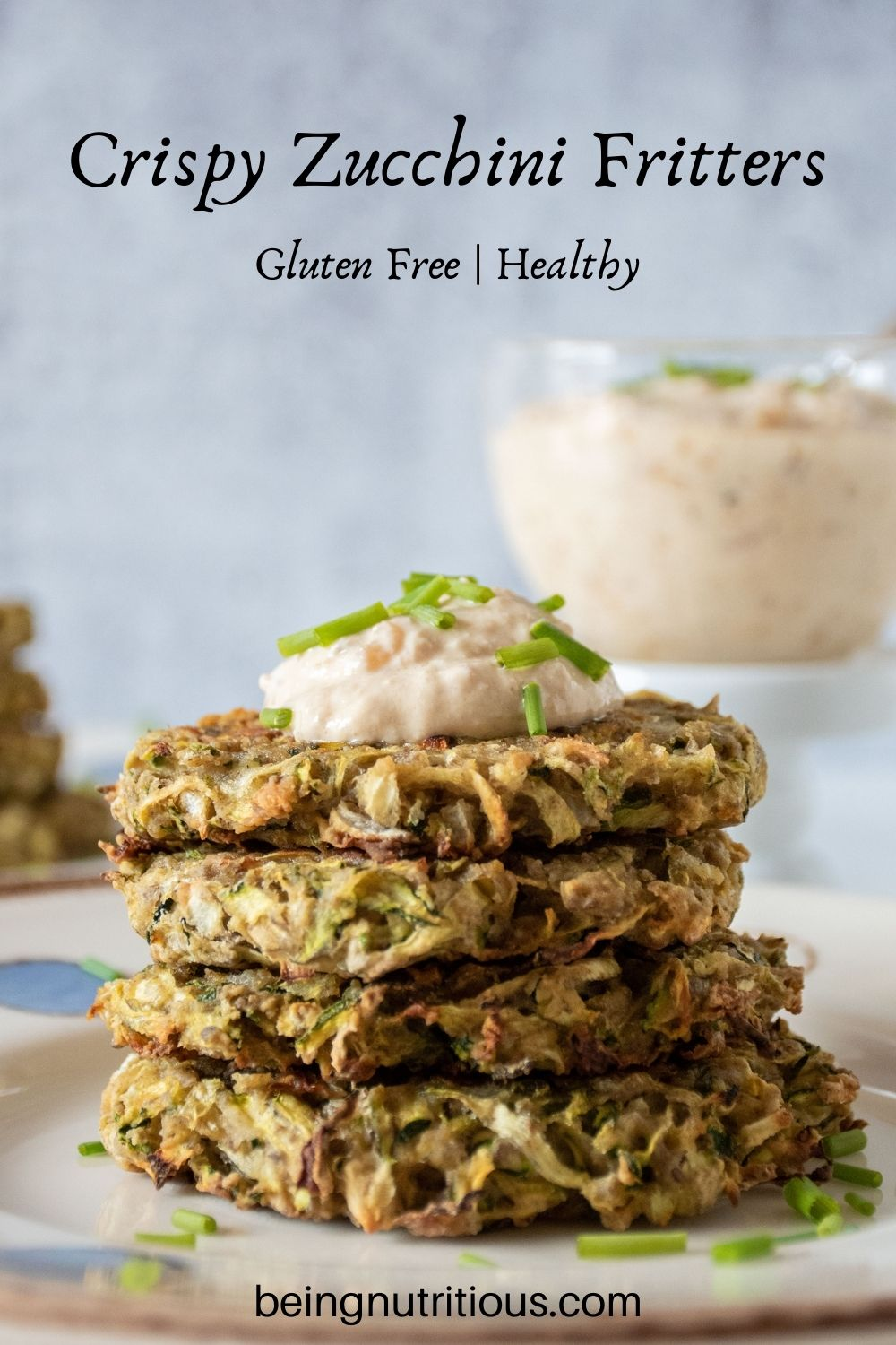 Stack of 4 zucchini fritters with a dollop of dip on top, garnished with chopped chives. Text overlay: Crispy Zucchini Fritters; gluten free, healthy.