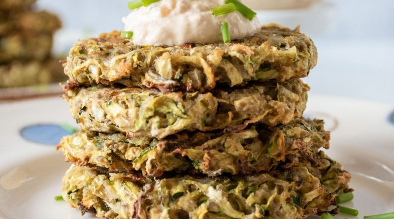 Stack of 4 zucchini fritters with a dollop of dip on top, garnished with chopped chives.