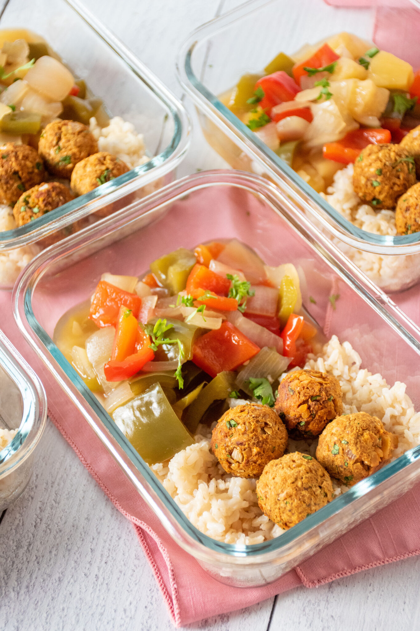 Glass meal prep containers, filled with rice, meatballs, and onions and peppers.