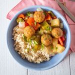 Bowl with rice, meatballs, and onions and bell peppers.