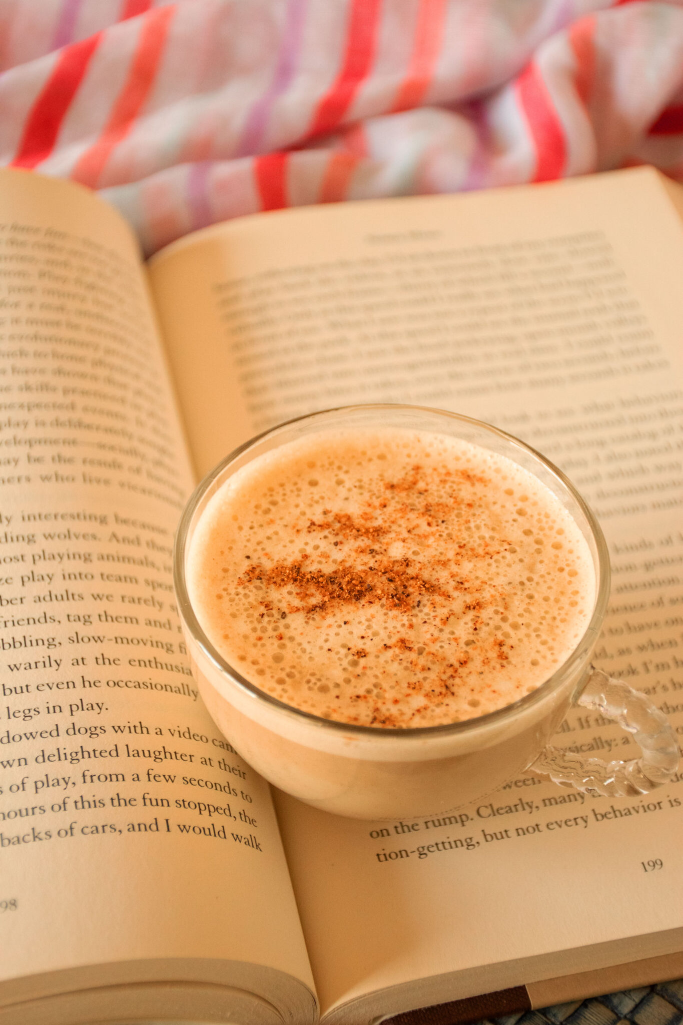 Small glass cup of latte sitting on an open book.
